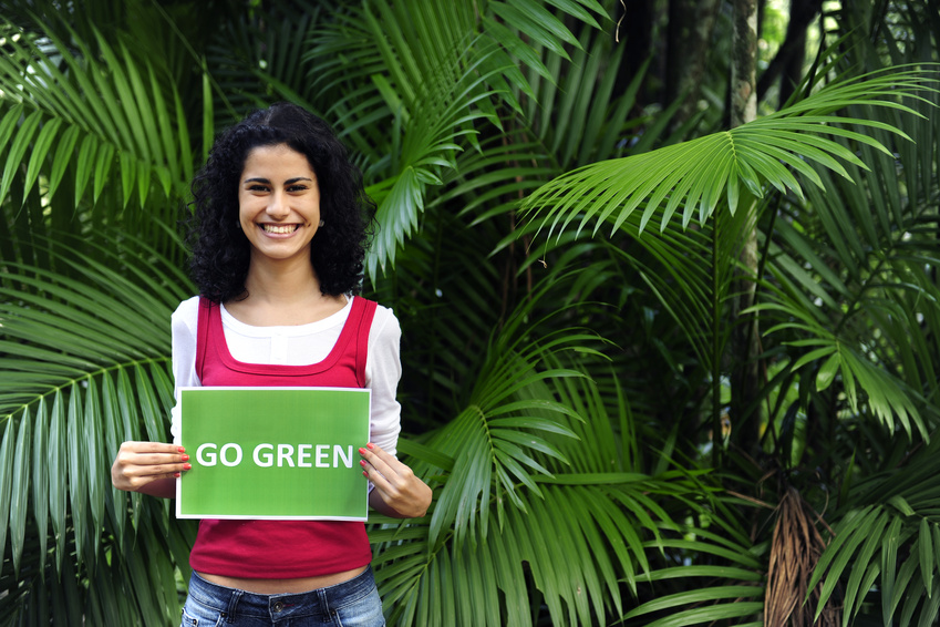 woman in the forest holding a go green sign
