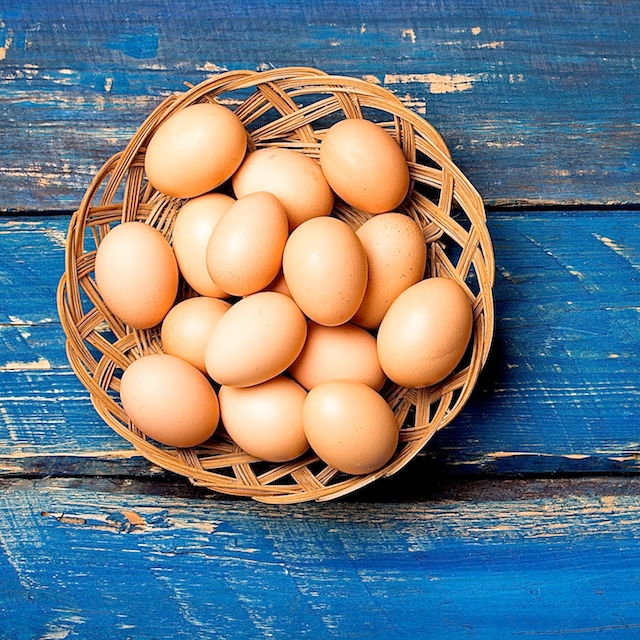 chicken eggs in a basket on a blue wooden table